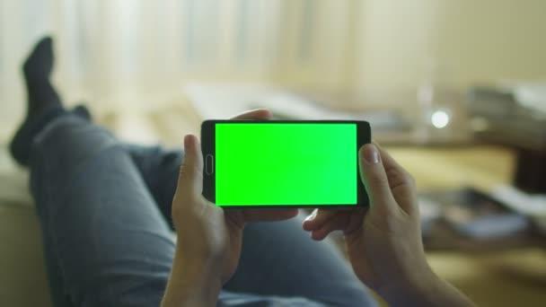 Člověk leží na gauči doma a držení telefonu Android s Green Screen v režimu na šířku