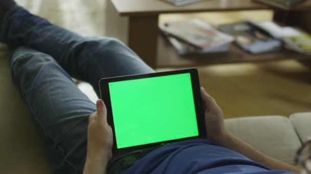 Člověk je pokládání na gauči doma a sledovat na tabletu s Green Screen v režimu na šířku