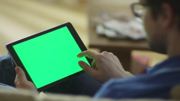 Člověk leží na gauči doma a použití tabletu s Green Screen v režimu na šířku