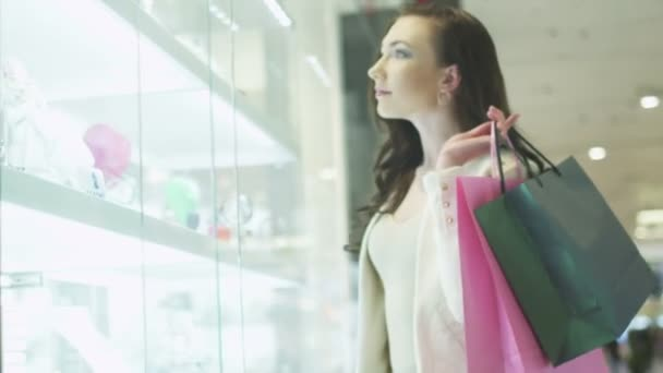 Young Pretty Girl with Shopping Bags is Looking at Display Window of Jewelry Store in Shopping Mall. Handheld Shot