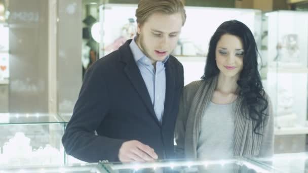 Mladý pár v klenotnictví je pozorování v zobrazení oken