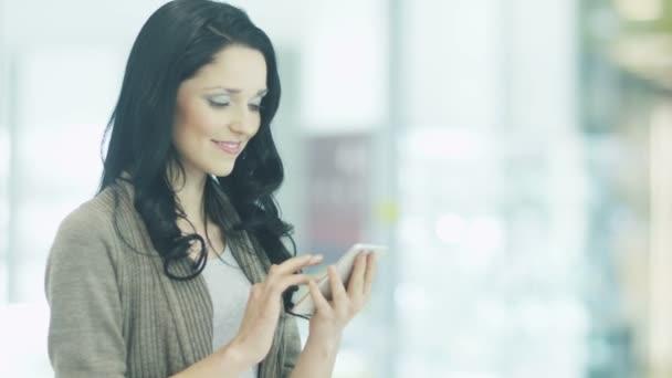 Mladé dívky jsou používání mobilního telefonu v nákupní centrum