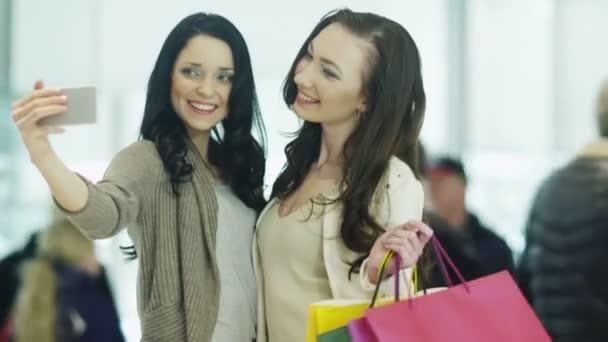 Dvě dívky se dělají Selfie s telefonem v nákupní centrum