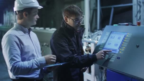 Engineer and Factory Worker are Setting Up CNC Lathe Machine Together
