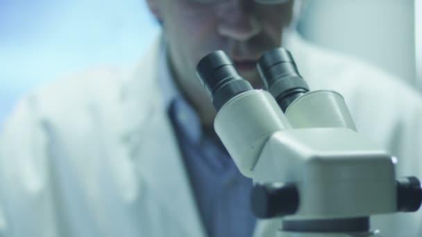 Vědec provádí výzkum a vypadá přes mikroskop