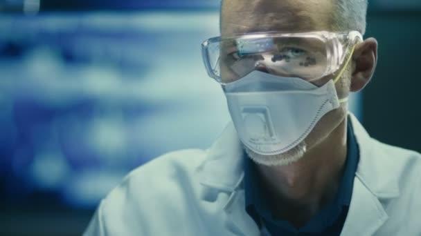 Porträt eines Wissenschaftlers mit Schutzbrille und Atemmaske. Blick in die Kamera