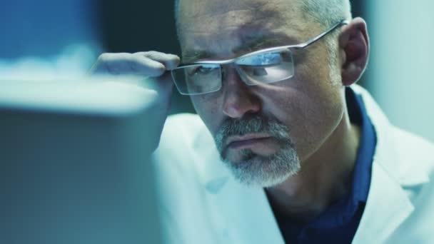 Seriöser und fokussierter Wissenschaftler, der am Computer arbeitet.