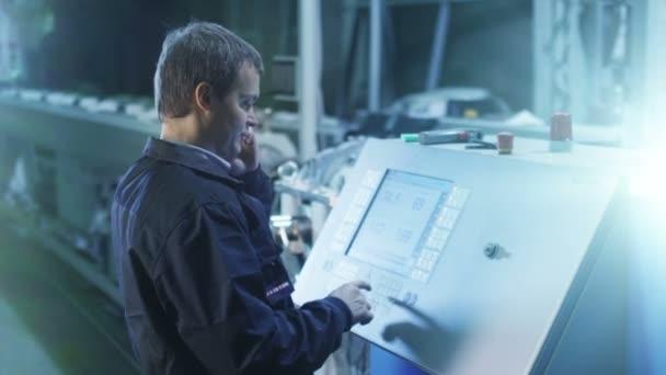 Inženýr je nastavení se Cnc soustruh stroj v továrně a mluvit na telefonu