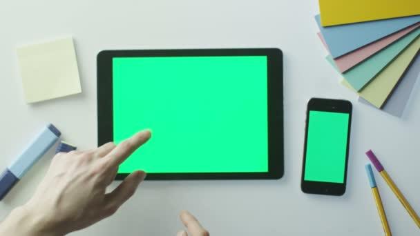 Designer nutzt Tablet und Handy mit grünem Bildschirm.