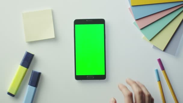 Designer is Using Android Phone with Green Screen in Portrait Mode