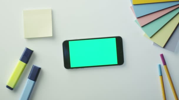 Designer verwendet Mobiltelefon mit grünem Bildschirm im Querformat. Ansicht von oben.