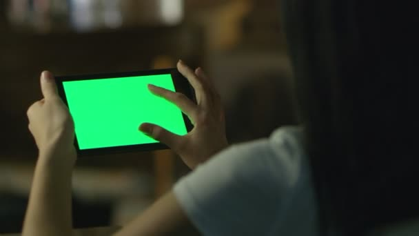 Teen Girl is Using Tablet PC with Green Screen in Landscape Mode at Evening. Casual Lifestyle.
