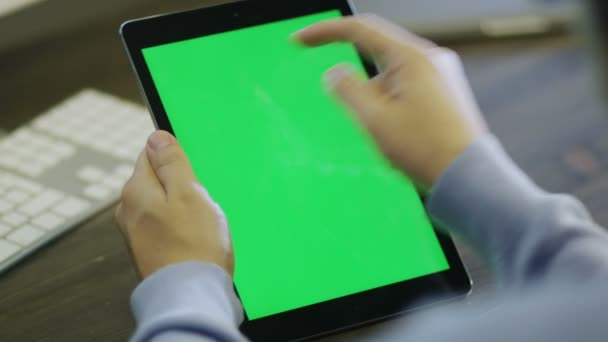 Designer using Digital Tablet with Green Screen in Portrait Mode at Work.