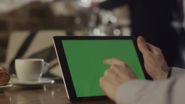 Férfi tabletta kávézóban. Zöld képernyő tabletta
