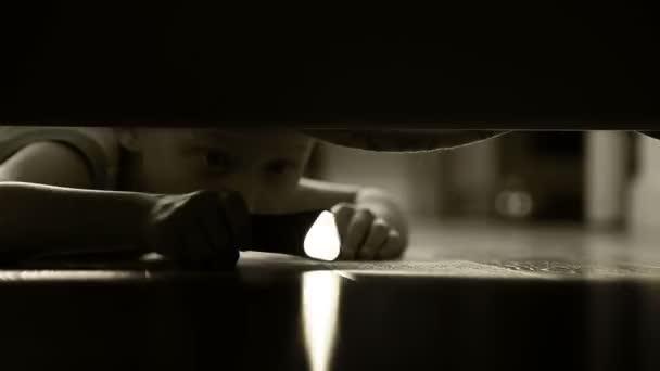 ein kleiner Junge mit Pocket Torch, tastend um unter dem Bett