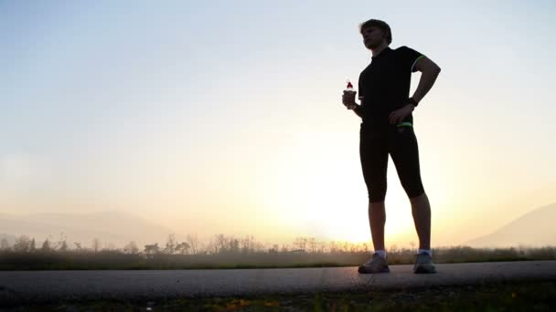 Marathon runner drinks water on the wide angle mountain landscape