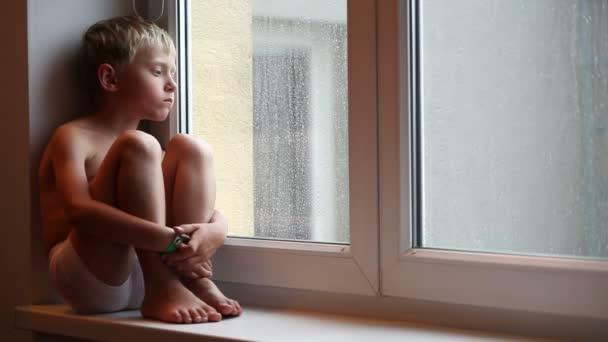 Fiú ül az ablakpárkányon