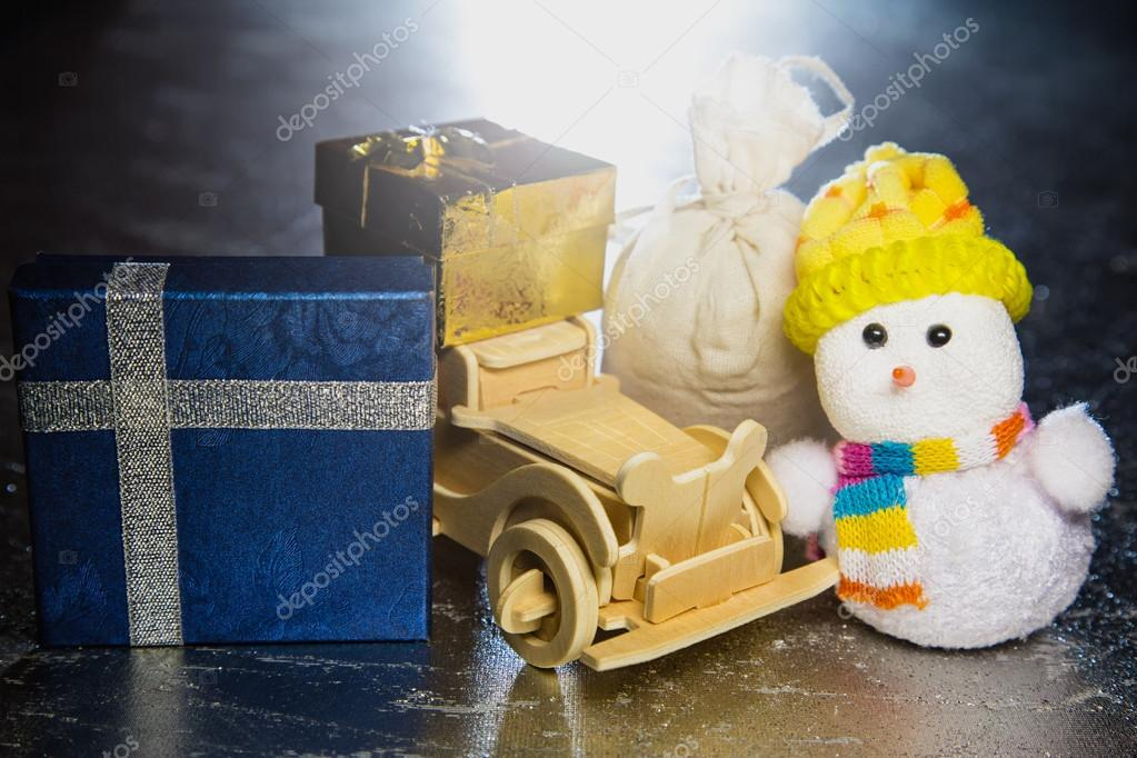 Snowman with wooden car, gift boxes and sack