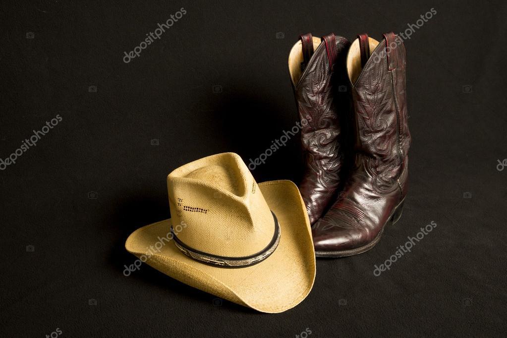Botas vaqueras y sombrero de vaquero sobre fondo negro– imagen de stock 1f4a109bb14