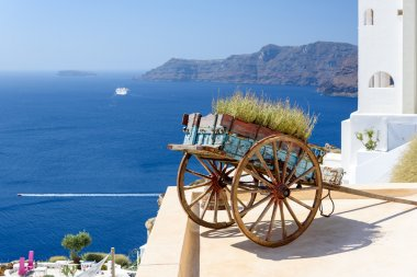 Decorative old cart with flowers on a roof terrace in Oia, Santorini