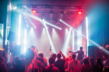 Color disco club light with laser show and dancing people