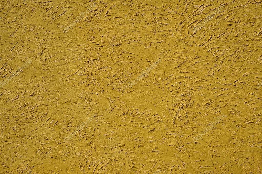 The texture of mustard color walls painted large erratic