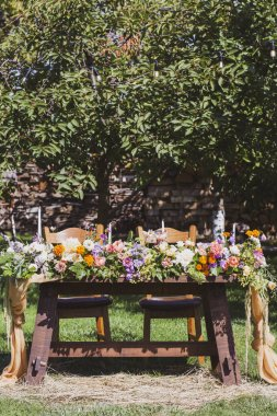 Banquet tables in nature. Wedding in the garden. Outdoor wedding. Buffet. Wedding banquet in nature.Festive table serving dishes stands on green grass. table compositions, glasses, candles and plates are placed on table