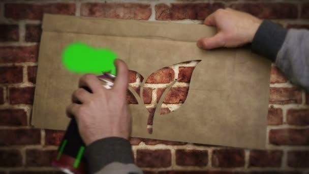Eco ikona sprej namalovaný na cihlové zdi. Graffiti umění koncept ekologie přátelský a životní prostředí list symbol. Městská abstraktní tvorba. Airbrush barva se znakovou šablonou v ruce.
