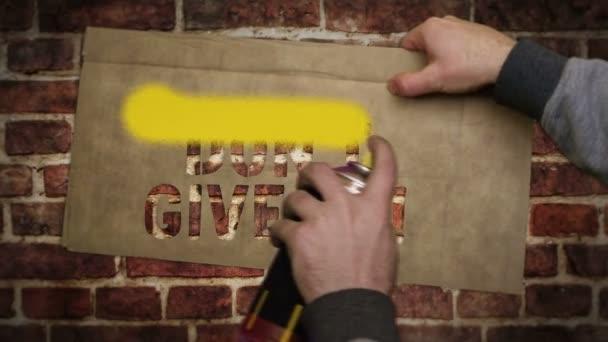 Nevzdávej se nápisu namalovaného na cihlové zdi. Graffiti umělecká koncepce pozitivní motivace a vytrvalost. Městská abstraktní tvorba. Airbrush barva se šablonou v ruce