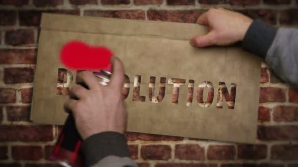 Revoluční sprej namaloval červený nápis na cihlovou zeď. Městská abstraktní tvorba. Graffiti umělecký koncept vzpoury, svobody, změny a lidských práv. Airbrush barva s textovou šablonou v ruce.