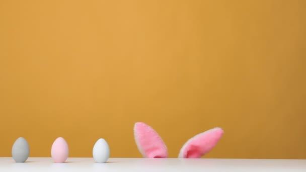 Boldog húsvétot! Vicces kislány vadászik az ünnepekkor. A gyerek kinéz az asztalról, és vesz egy tojást..
