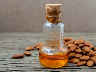Bottle of essential almonds oil with almonds on wooden backgroun