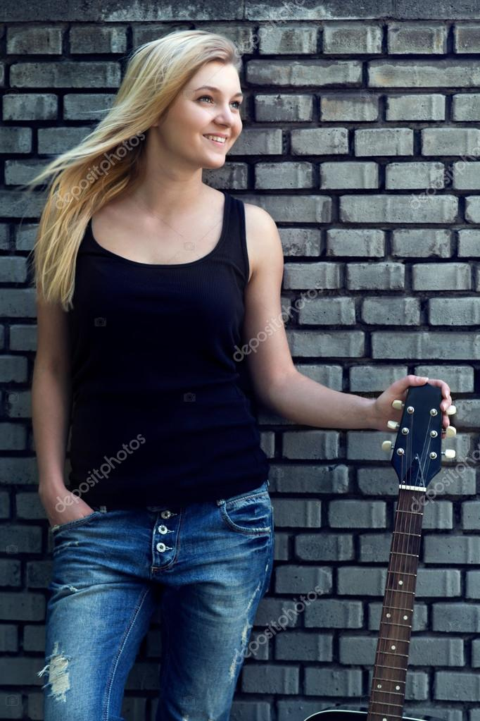 portrait of a woman with a guitar near brick wall