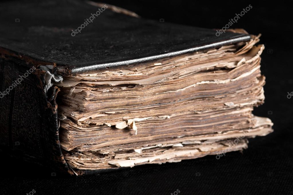 old thick book on a black background on the desktop stock photo