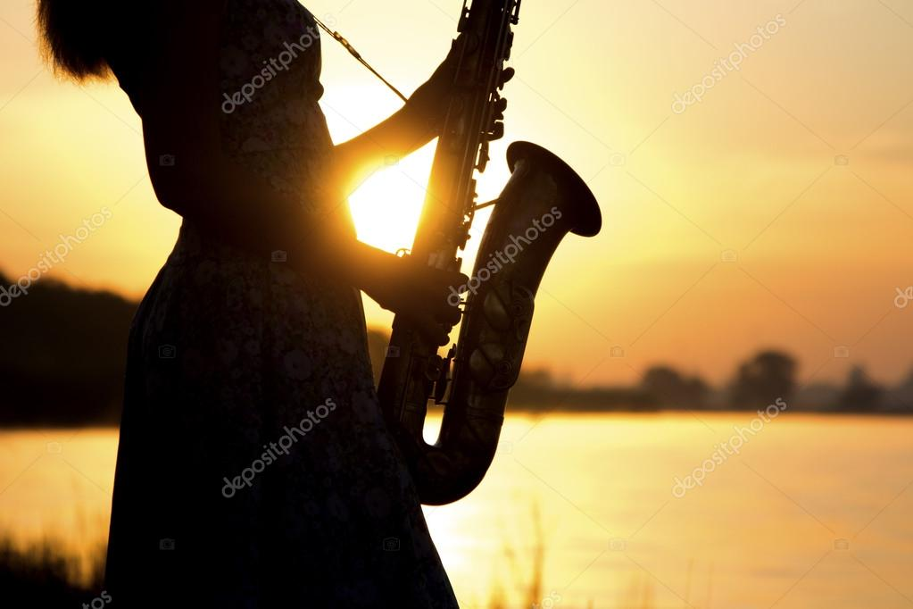 silhouette of a saxophone in hands of young woman near the river at sunset