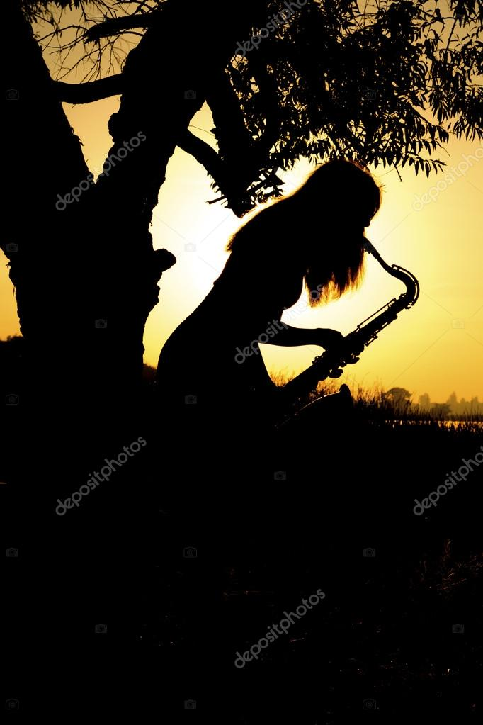 young woman playing the saxophone leaning on a tree is near a river in the background sunrise