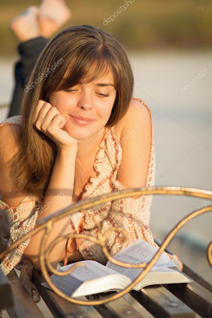 Young girl reading the Bible on a park bench