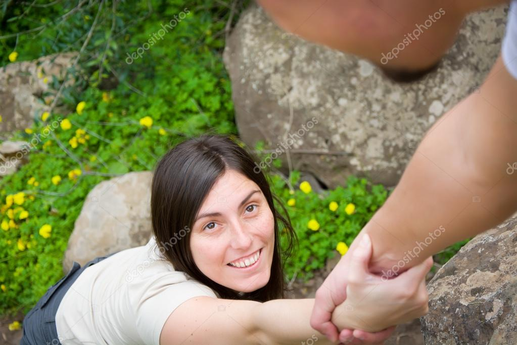 Man helping a woman climb a mountain