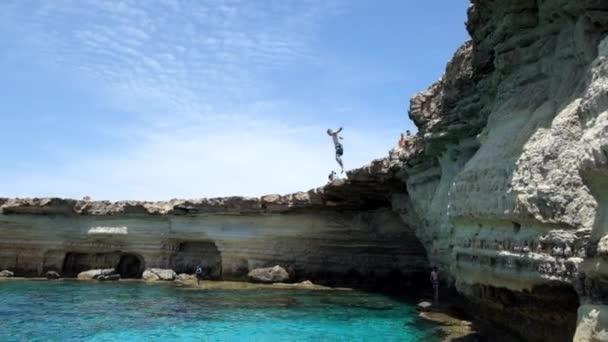 Muž skočí do moře z útesů v Cape Greco.Cyprus