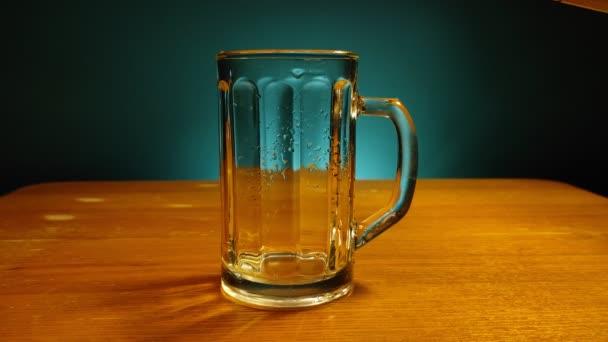 Pivo se nalévá do sklenice na dřevěném stole v modrém tónovaném pozadí.
