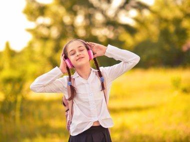 Beautiful little girl listening to music on headphones in autumn park. Schoolgirl in outdoors.