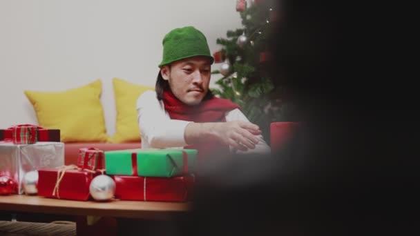 Atraktivní asijské muži zaškrtnutí dárkové krabice zdobí vánoční stromeček slaví nový rok v obývacím pokoji doma. Koncept Vánoční oslavy.