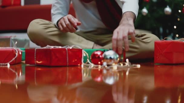 Mladý Asiat dělá dárkovou krabici v obývacím pokoji doma s vánoční stromeček na pozadí. Koncept Vánoční oslavy.
