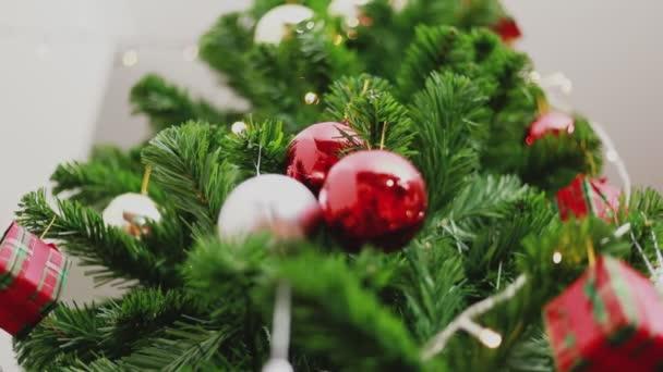 Mladá asijská žena držící malé červené koule zdobí vánoční stromeček slaví nový rok v obývacím pokoji doma. Koncept Vánoční oslavy.