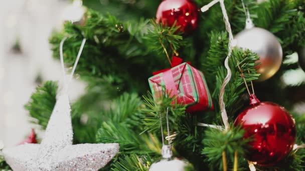 Pravá kamera se zaměřuje na vánoční míče a ozdoby vánoční stromeček oslavuje nový rok v obývacím pokoji doma. Koncept Vánoční oslavy.