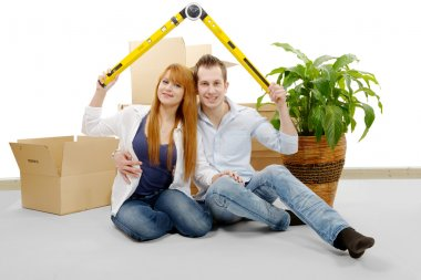 smiling young couple sitting after moving house