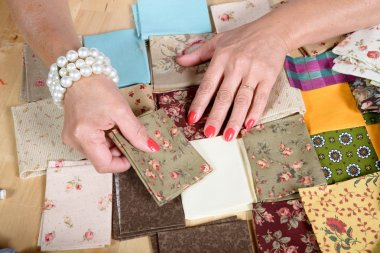 Close up of woman's hand sewing patchwork