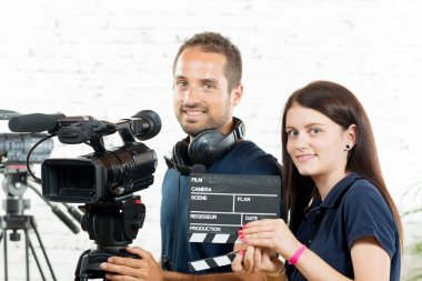 a young man and a young woman with a movie camera