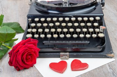 old typewriter with a red rose