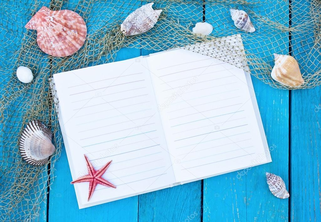 Open notebook on old blue wooden table with fishing net, cockles